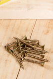 Pile of metar screws on the wooden planks background Royalty Free Stock Image