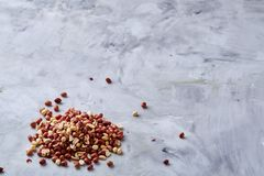 Pile of mixed raw peelled peanuts on white textured background, background, top view, close-up, selective focus. Some copy space. Organic nutritious ingredient royalty free stock photo