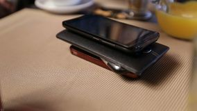 Pile of mobile phones on the table in cafe. Royalty Free Stock Image