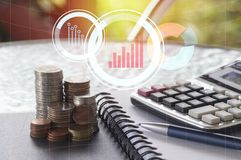 Pile of money coin with calculator, book and pen, concept in finance Stock Images