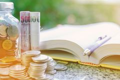 Pile of money coins in and outside the glass jar and Thai currency banknote with opened book and a pen on blurred natural green b. Ackground and sunlight effect stock image