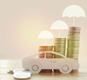 Pile of money coins, umbrella and paper car. Concept in insurance,loan,finance and buying vehicles Royalty Free Stock Photos