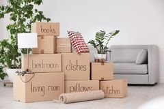 Pile of moving boxes and household stuff. In living room royalty free stock photo