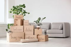 Pile of moving boxes and household stuff. In living room royalty free stock image