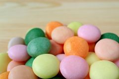 Pile of Multi-Colored Round Candies on Wooden Background with Selective Focus stock photos
