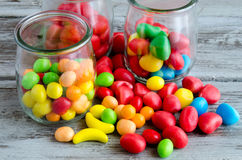 Pile of multicolored candies with glass jars Stock Image