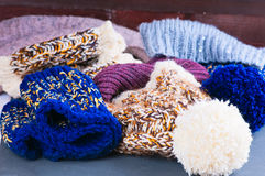 Pile of multicolored knitted woolen scarves and warm hats Stock Photo