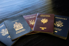 A pile of multinational passports. A stack of passports from Canada, Russia, Ukraine, and the United States royalty free stock photo