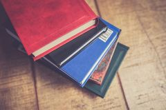 Pile of multiple color books on wooden table Stock Photography