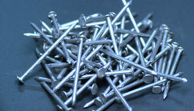 Pile of nails. Large pile of silver colored steel nails isolated on blue background Royalty Free Stock Photo
