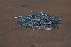 A pile of nails on a sheet of iron. Royalty Free Stock Photography