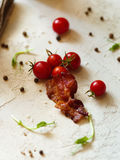 A pile of natural, fresh small tomatoes and a piece of bacon on Royalty Free Stock Photos