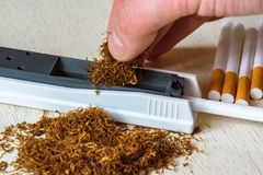 A pile of natural tobacco on a white wooden table and a device for manual cigarette making. Smoking. stock photo