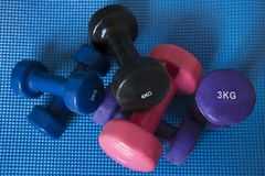 A pile of neoprene coated iron dumbbells of different weights. Horizontal shot of pile of sport equipment used for muscle toning, aerobic and weight training Royalty Free Stock Image