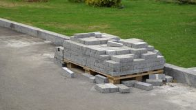 Pile of new bricks lies on ground near green grass lawn in park. Landscape design, improvement of cityscape and city planning. Parks, outdoors and design stock footage