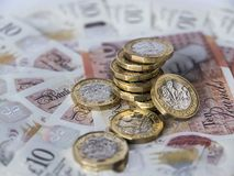 Stack of new pound coins on ten pound notes Stock Images