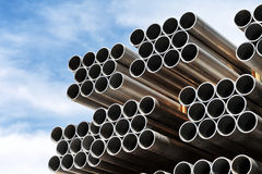Pile of new steel pipes on a construction site. Pile of new steel pipes waiting to be installed on a construction site, low angle view of open ends against blue royalty free stock photos