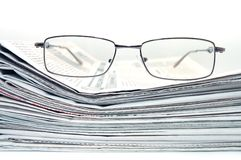 Pile of newspaper with eyeglasses. Pile of newspaper with eyeglass stock photos