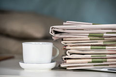 Pile of newspapers and coffee cup Royalty Free Stock Images
