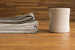A pile of Newspapers and a Cup on a wooden table Stock Photo