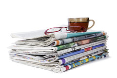 Pile of newspapers with glasses and a cup of tea. Stock Image