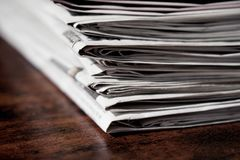 Pile of newspapers or papers. On wooden table - print media news stock photos