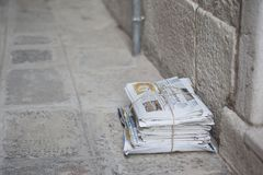 A pile of newspapers, tied with string. Sat on the pavement in a street in Venice, Italy. royalty free stock photos