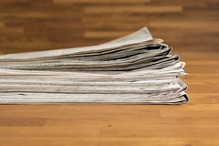 A pile of Newspapers on a wooden table Royalty Free Stock Photos
