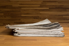 A pile of Newspapers on a wooden table Stock Photos
