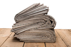 Pile of newspapers on a wooden table Royalty Free Stock Photo