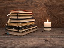 A pile of notebooks and a candle on a wooden table royalty free stock photo