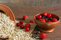 Pile of oat flakes and berries in pottery on canvas on the table Royalty Free Stock Image