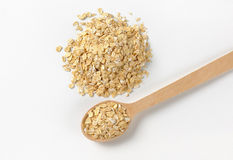 Pile of oat flakes. And wooden spoon on white background Royalty Free Stock Image