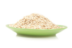 Pile of oatmeal on a green plate Royalty Free Stock Photography