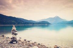 Free Pile Of Balanced Pebbles On The Bank Of Lake Mirroring Sky Royalty Free Stock Photo - 215408045