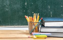 Free Pile Of Books With Notes Paper And Pen With Pencils In Basket Container On Wooden Table With Chalkboard Background Stock Images - 148807414