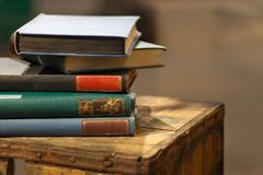 Stock of old books. Pile of unorganized vintage book on the wooden crate royalty free stock photography