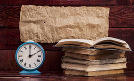 Pile of old books with alarm clock Stock Photography