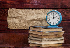 Pile of old books with alarm clock Stock Image