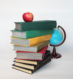 Pile of old books with apple on top and globe Royalty Free Stock Images