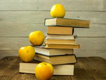 Pile of old books and apples on wooden background royalty free stock image
