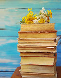 Pile of old books with a bouquet of yellow flowers tansy and yarrow. On a blue background royalty free stock photography