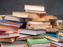 Pile of old books. Closeup of pile of old books over gray wall Royalty Free Stock Photos