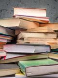 Pile of old books. Closeup of pile of old books over gray wall Royalty Free Stock Image