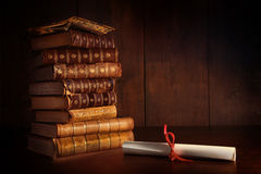 Pile of old books on desk. Pile of old books and diploma on desk Royalty Free Stock Images