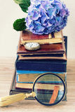 Pile of old books with flowers and clock Stock Image