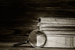 A pile of old books and magnifier Stock Photography