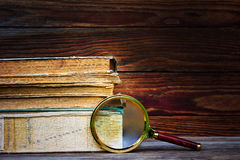 A pile of old books and magnifier on wooden background Stock Image