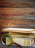 A pile of old books and magnifier Stock Photos