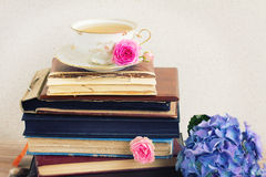 Pile of old books and mail with cup of tea Royalty Free Stock Image